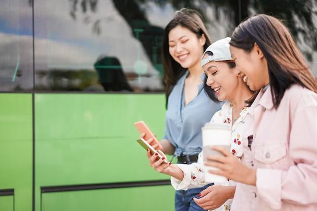 Glückliche asiatische freunde, die smartphones am busbahnhof verwenden. junge studenten, die spaß mit telefon-app nach der schule haben Premium Fotos