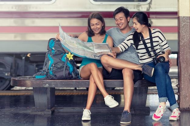 Glückliche asiatische freunde gruppieren die sitzende planung für reisende zusammen an der bahnstation und schauen die karte. Premium Fotos
