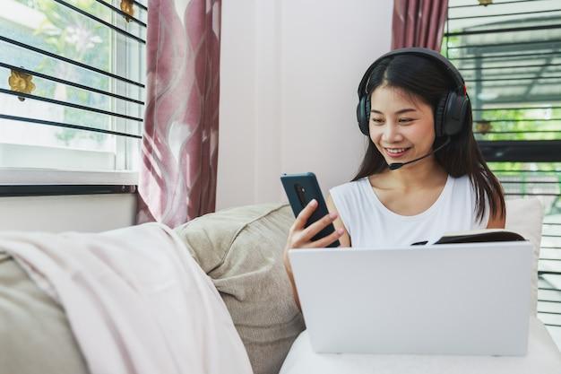 Glückliche asiatische geschäftsfrau, die handy und laptop für arbeit von zu hause aus verwendet Premium Fotos