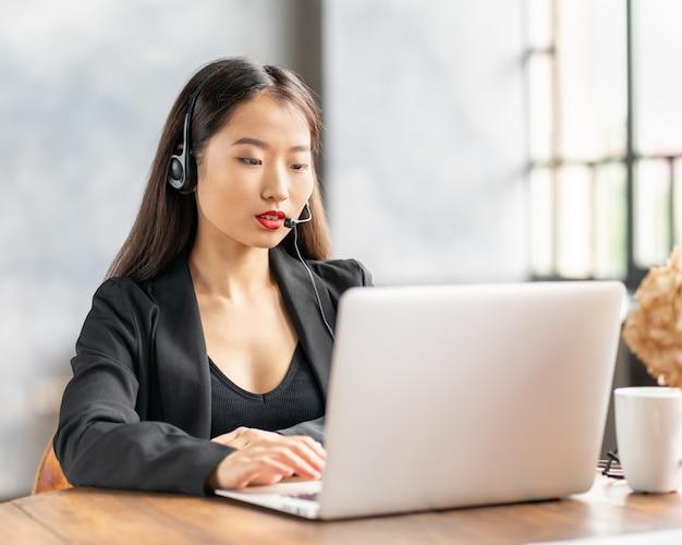 Glückliche asiatische geschäftsfrau im headset, das durch telefonkonferenz und video-chat auf laptop im büro spricht Premium Fotos