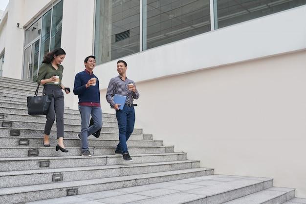 Glückliche asiatische geschäftsleute, welche die kaffeepause verlässt das bürogebäude für kurze promenade haben Kostenlose Fotos