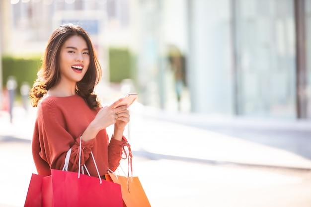 Glückliche asiatische hübsche frau, die einkaufstaschen hält, während smartphone verwendet Premium Fotos