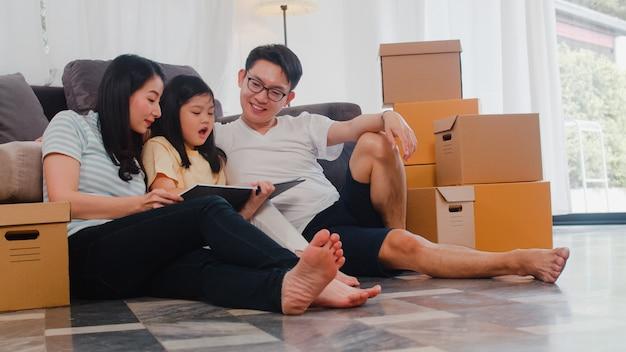 Glückliche asiatische junge familienhausbesitzer kauften neues haus. chinesische mutter, vati und tochter, die das vorwärtsschauen zur zukunft im neuen haus umfassen, nachdem sie in den umzug umgezogen sind, der zusammen auf boden mit kästen sitzt. Kostenlose Fotos