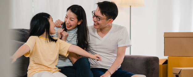 Glückliche asiatische junge familienhausbesitzer kauften neues haus. die japanische mutter, der vati und die tochter, die freuen sich auf zukunft im neuen haus umfassen, nachdem sie in den umzug umgezogen sind, der zusammen auf sofa mit kästen sitzt. Kostenlose Fotos