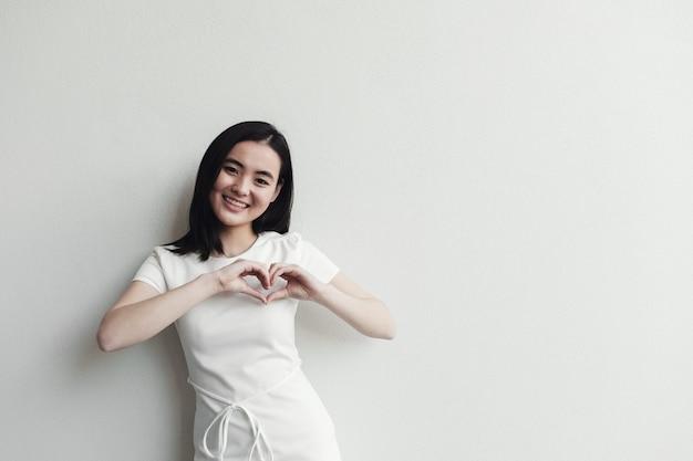 Glückliche asiatische junge frau, die ihre hände in der herzform macht Premium Fotos