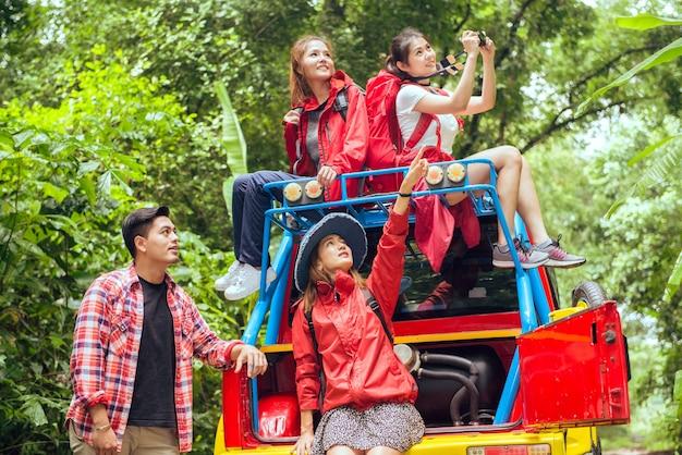 Glückliche asiatische junge reisende mit 4wd fahren auto weg von der straße im wald, junges paar, das nach richtungen auf der karte sucht und zwei andere genießen auf 4wd antriebsauto. junge gemischte rasse asiatische frau und mann. Premium Fotos