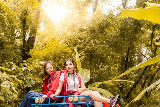 Glückliche asiatische junge reisende mit 4wd fahren auto weg von der straße im wald Premium Fotos
