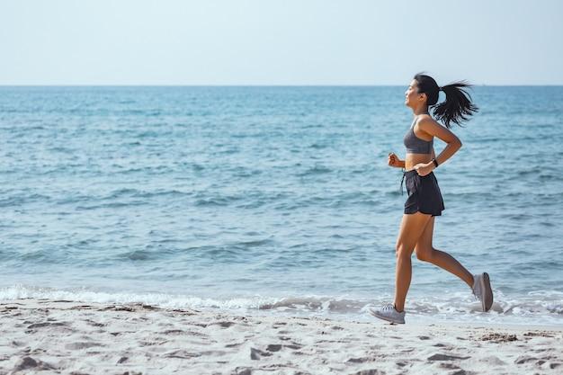 Glückliche asiatische läuferfrau laufen allein am strand Premium Fotos