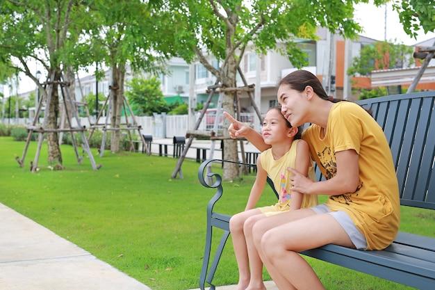 Glückliche asiatische mutter und tochter entspannend sitzen auf bank im garten im freien. mutter zeigt etwas mit kindermädchen, das im sommerpark schaut. Premium Fotos