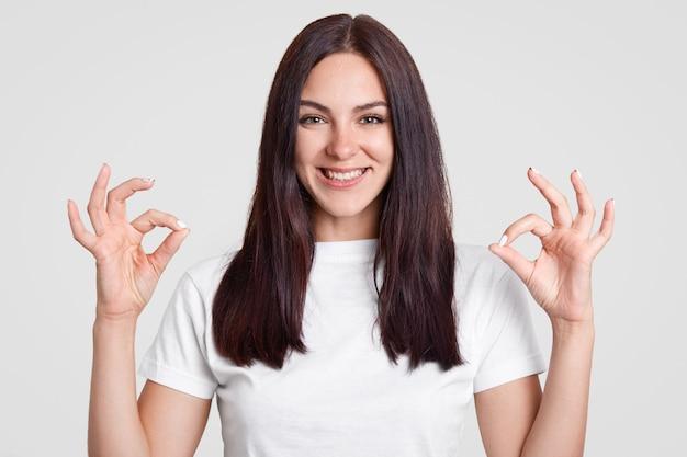 Glückliche attraktive frau mit langen glatten dunklen haaren, macht okay zeichen mit beiden händen, zeigt zustimmung Kostenlose Fotos