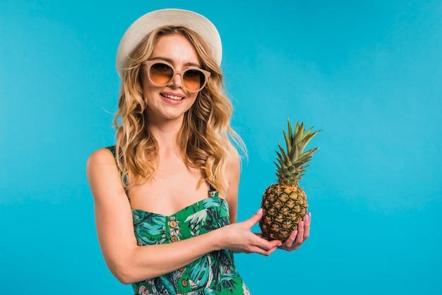Glückliche attraktive junge frau im kleid mit dem hut und sonnenbrillen, die frische ananas halten Kostenlose Fotos