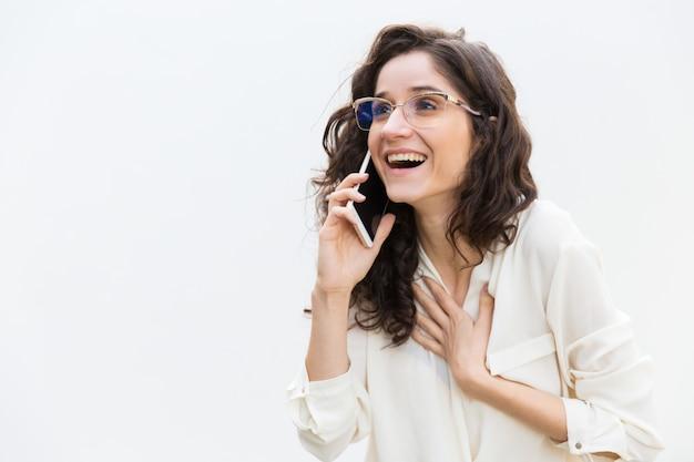 Glückliche aufgeregte frau in den gläsern sprechend auf mobiltelefon Kostenlose Fotos
