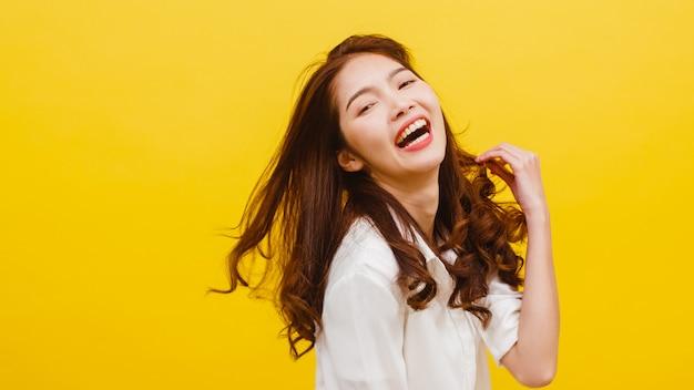 Glückliche aufgeregte junge lustige asiatische dame, die musik hört und in der freizeitkleidung über gelber wand tanzt. menschliche gefühle, gesichtsausdruck, studioporträt, lebensstilkonzept. Kostenlose Fotos