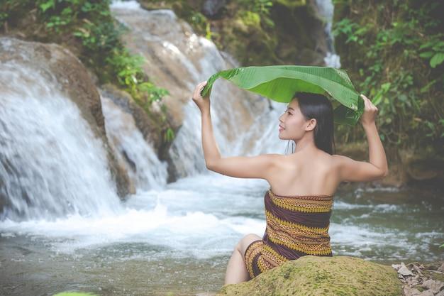 Glückliche badende frauen am natürlichen wasserfall Kostenlose Fotos