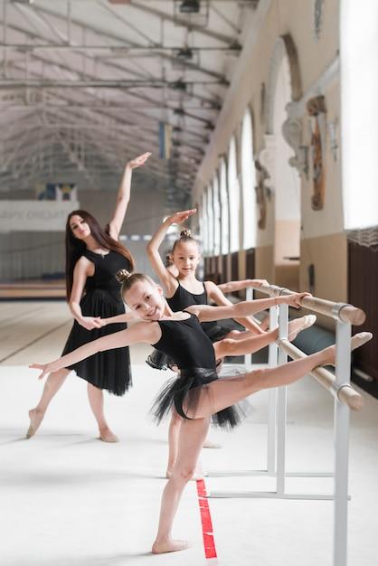 Glückliche ballerinamädchen, die ballett auf barre mit ihrem trainer üben Kostenlose Fotos