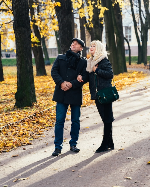 Glückliche blonde fällige frau und schöner brunette von mittlerem alter, schauen oben zum himmel und gehen in park Premium Fotos