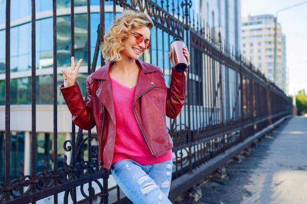 Glückliche blonde frau, die auf modernen straßen aufwirft, kaffee oder cappuccino trinkend. stilvolles herbstoutfit, lederjacke und strickpullover. rosa sonnenbrille. Kostenlose Fotos