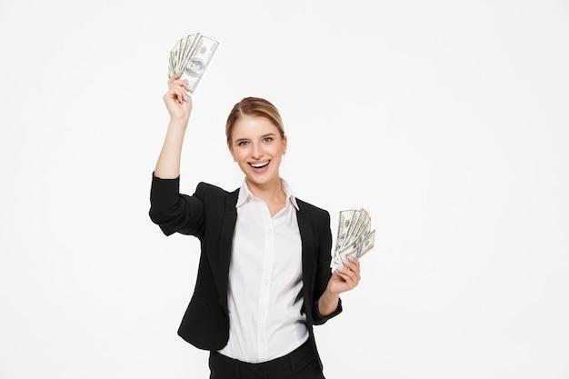 Glückliche blonde geschäftsfrau, die geld in den händen und mit offenem mund über weißer wand hält Kostenlose Fotos