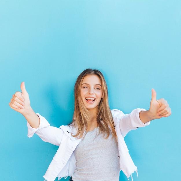 Glückliche blonde junge frau, die daumen herauf zeichen gegen blauen hintergrund zeigt Kostenlose Fotos