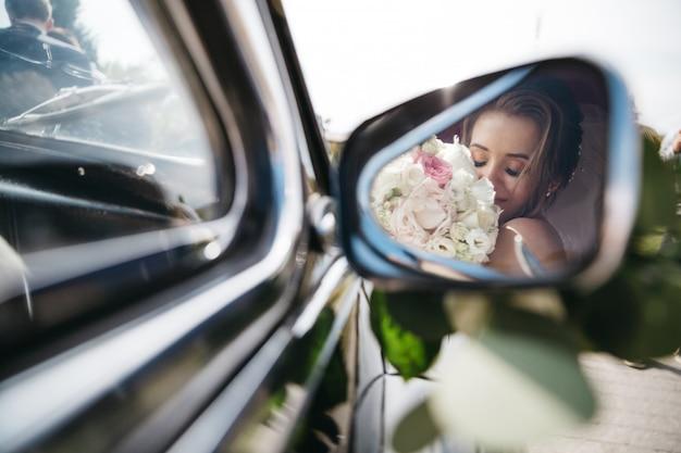 Glückliche braut schnüffelt blumen im auto Kostenlose Fotos