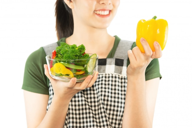 Glückliche dame, die küchenmaterial über kopienraumhintergrund hält Kostenlose Fotos