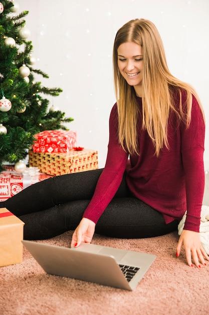 Glückliche dame, die laptop nahe geschenkboxen und weihnachtsbaum verwendet Kostenlose Fotos