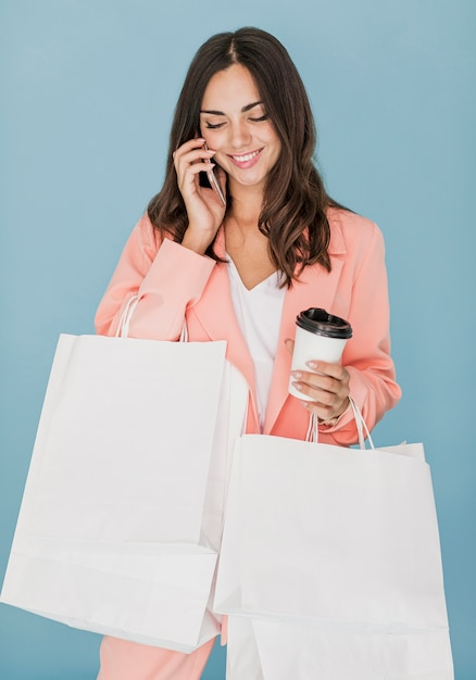 Glückliche dame mit einkaufsnetzen sprechend am smartphone Kostenlose Fotos