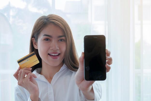 Glückliche darstellende kreditkarte und smatrphone der geschäftsfrau, zum für das on-line-einkaufen zu zahlen. Premium Fotos
