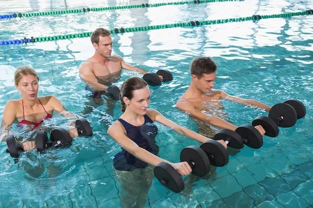 Glückliche eignungsklasse, die aqua aerobic mit schaumdummköpfen im swimmingpool in der freizeitmitte tut Premium Fotos