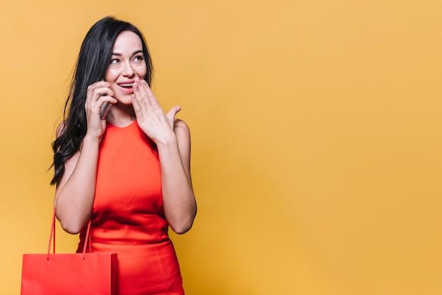 Glückliche einkaufsfrau, die telefonanruf hat Kostenlose Fotos