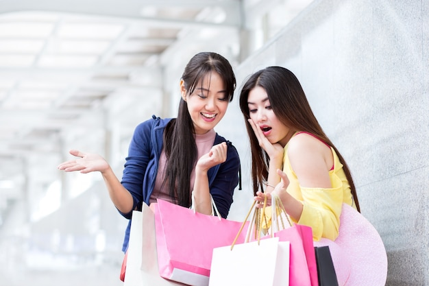 Glückliche einkaufsfrauen oder frau mit freund, mit einkaufstasche im sommerschlussverkauf des speichers herein in die stadt Premium Fotos