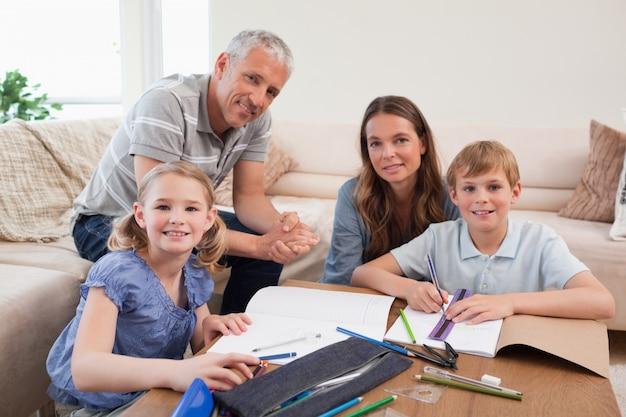 Glückliche eltern, die ihren kindern helfen, ihre hausarbeit zu tun Premium Fotos