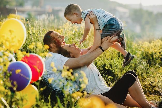 Glückliche eltern haben spaß mit ihrem kind auf grünem rasen unter dem baum Kostenlose Fotos