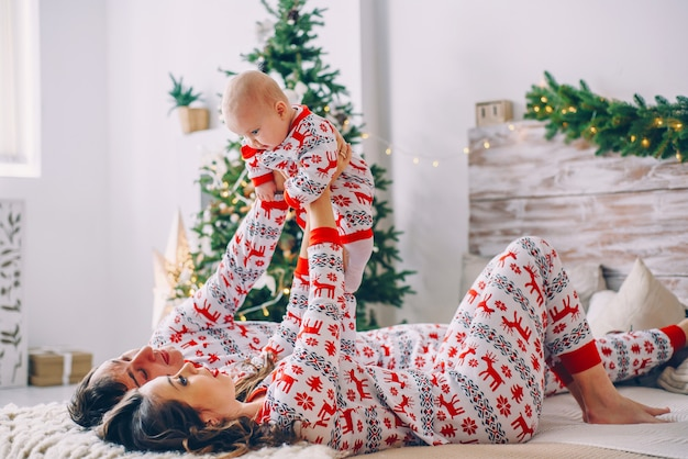 Glückliche eltern mit ihrer kleinen tochter in der feiertagskleidung mit den druckrotwild und schneeflocken, die spaß auf dem bett im gemütlichen raum mit einem weihnachtsbaum haben Premium Fotos