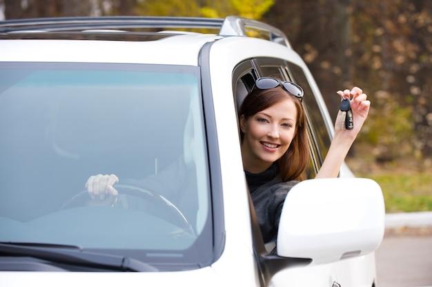 Glückliche erfolgreiche frau mit schlüsseln vom neuen auto Kostenlose Fotos