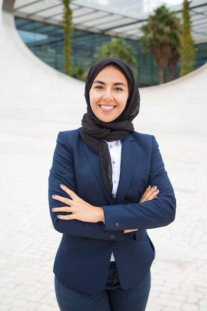 Glückliche erfolgreiche moslemische geschäftsfrau, die draußen aufwirft Kostenlose Fotos