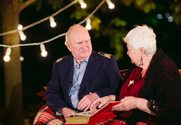 Glückliche erinnerungen. glückliche ältere paare, die auf überwachendem album des sofas mit fotos sitzen. Premium Fotos