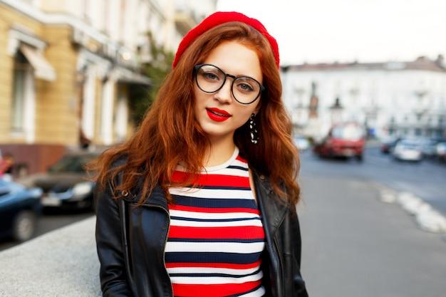 Glückliche fabelhafte ingwerfrau in der stilvollen roten baskenmütze in der straße Kostenlose Fotos
