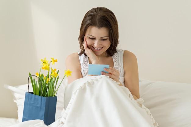 Glückliche fällige frau, die das geschenk der blumen genießt und grußkarte liest Premium Fotos