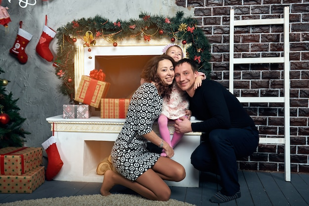 Glückliche familie am kamin für die winterferien. heiligabend und silvester. Premium Fotos