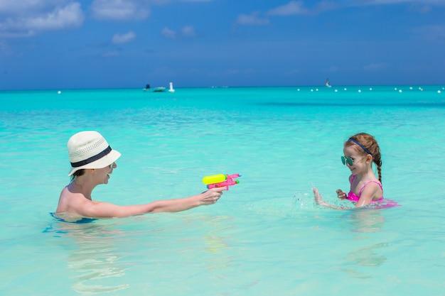 Glückliche familie am tropischen strand, der spaß hat Premium Fotos