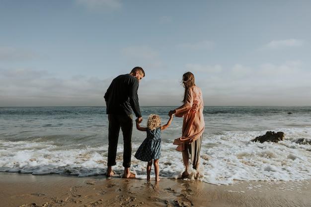 Glückliche familie an einem strand Kostenlose Fotos