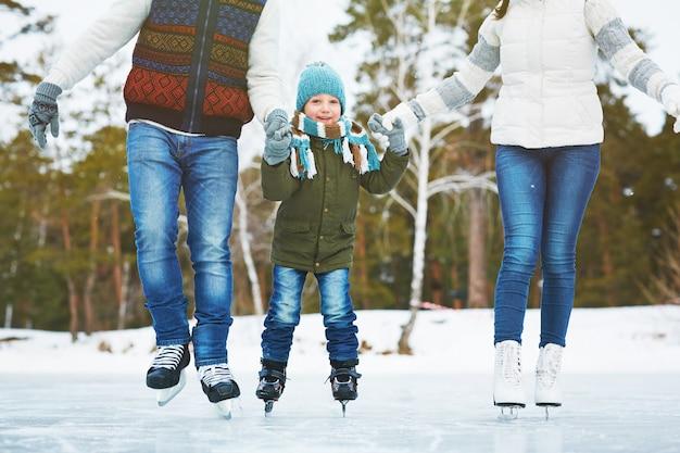 Glückliche familie auf der eisbahn Kostenlose Fotos