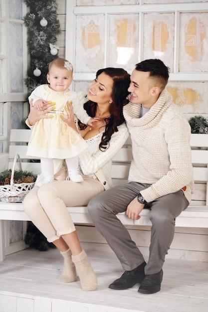 Glückliche familie auf der veranda mit weihnachtsdekorationen Premium Fotos