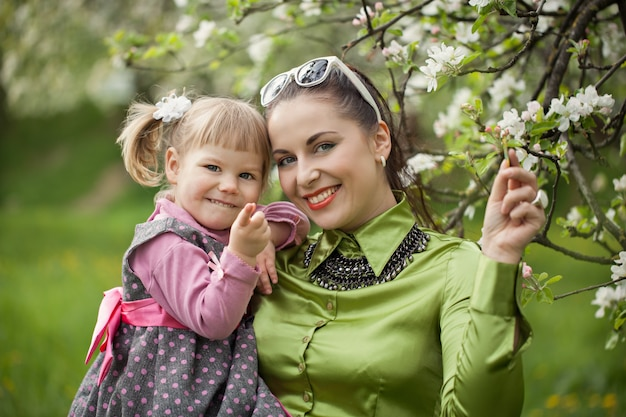 Glückliche familie auf mutter- und babytochter der natur draußen auf dem grünen garten Premium Fotos