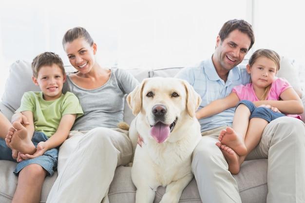 Glückliche familie, die auf couch mit ihrem haustier labrador sitzt Premium Fotos