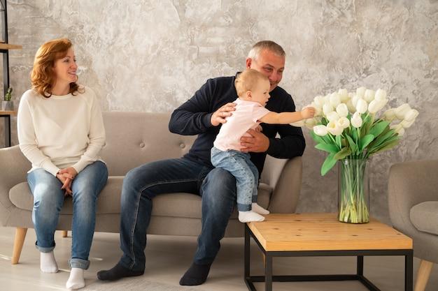 Glückliche familie, die auf dem sofa mit baby sitzt. großvater und großmutter verbringen ihren tag zusammen mit der enkelin im haus der familie Premium Fotos