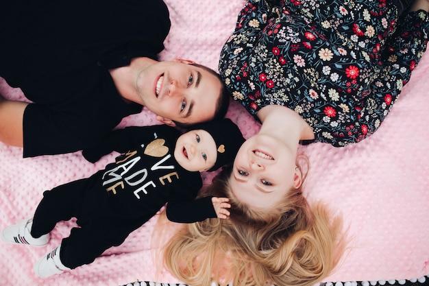 Glückliche familie, die auf rosa decke liegt Premium Fotos