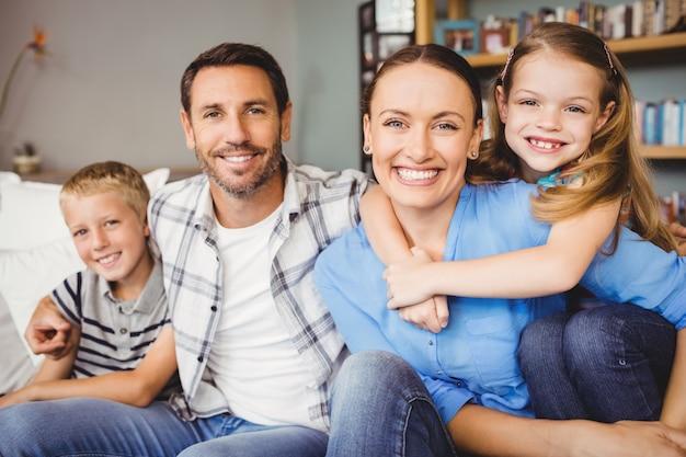 Glückliche familie, die auf sofa gegen regal sitzt Premium Fotos