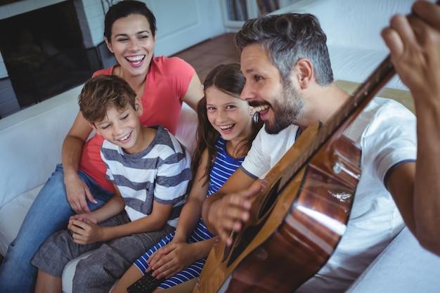 Glückliche familie, die auf sofa mit einer gitarre sitzt Premium Fotos